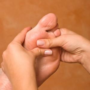 Physiotherapeutin massiert Fußreflexzonen eines Mannes