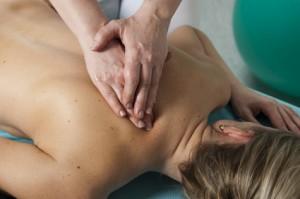 blonde Frau wird auf einer Massagebank therapiert