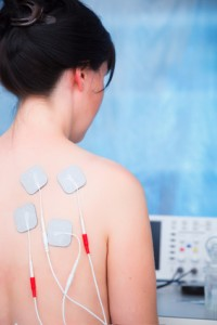 Woman with electrodes electric massage in physiotherapy room